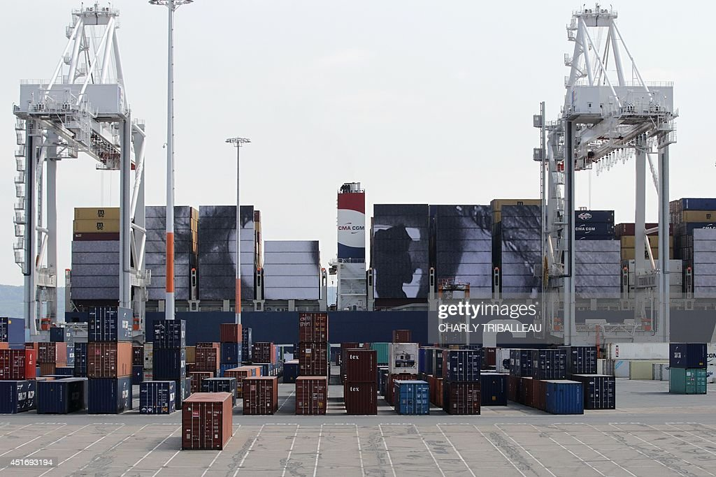 A gigantic collage by French artist and photographer JR is seen onto the CMA-CGM Magellan cargo ship on July 4, 2014 in Le Havre, northwestern France. A cargo boat displaying on its right flank a 5,000 m2 photo of the eyes of an African woman is leaving Le Havre on July 4 towards Malaysia. This gigantic collage is the new challenge of photographer JR, a specialist of artistic challenges. AFP PHOTO / CHARLY TRIBALLEAU.