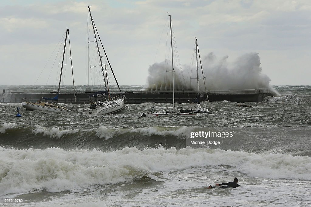 Gigantic waves crash over trawling vessels in front of a surfer at Mornington Harbour on May 3, 2016 in Melbourne, Australia. Wind gusts of up to 100km per hour are expected in Melbourne and parts of southern Victoria as part of a deep cold front moves across the state.