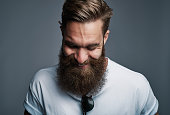 Single giggling attractive young European man with large furry beard with eyeglasses placed in shirt over gray background