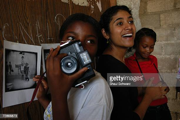 Gigi Cohen a photographer working in association with 'Kids With Cameras' helps 'restavek' children display their photographs after a class in...