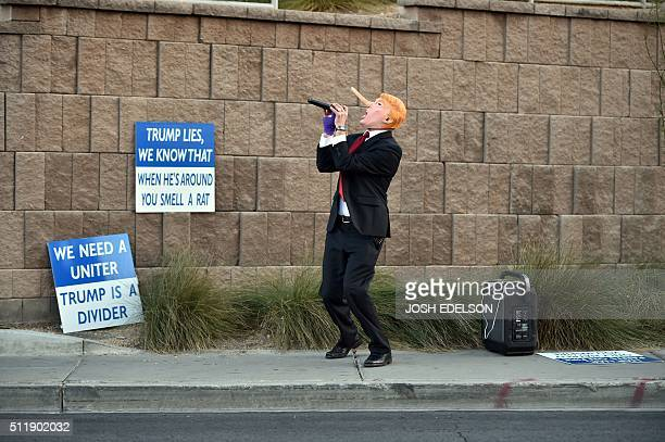 TOPSHOT Gil Mobley wears a Donald Trump costume while singing a song about him while protesters rally in front of the Trump Hotel in Las Vegas Nevada...