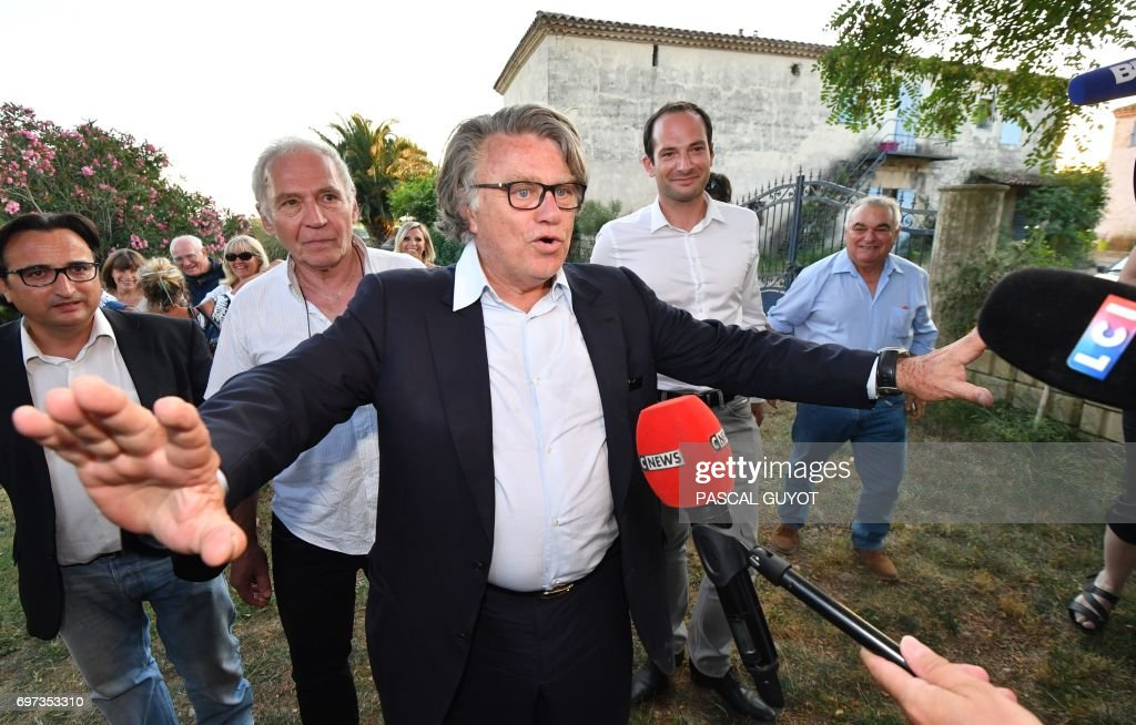 Gilbert Collard (C), French lawyer and far-right Front National (FN) party's candidate in the 2nd constituency of Gard department for the French parliamentary elections, reacts after winning in the second round on June 18, 2017 in Gallician, southern France. French President Emmanuel Macron's centrist party and its allies are on track for a huge majority in parliament, winning 355-425 seats in the 577-strong national assembly, polls showed on June 18. /