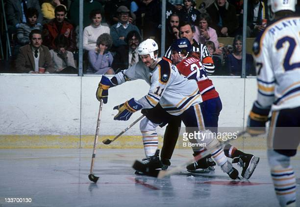 Gilbert Perreault of the Buffalo Sabres skates with the puck as Doug Jarvis of the Montreal Canadiens tries to check during their game on March 21...