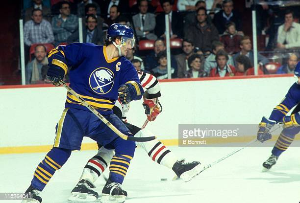 Gilbert Perreult of the Buffalo Sabres checks a player for the Chicago Blackhawks during their game circa 1987 at the Chicago Stadium in Chicago...
