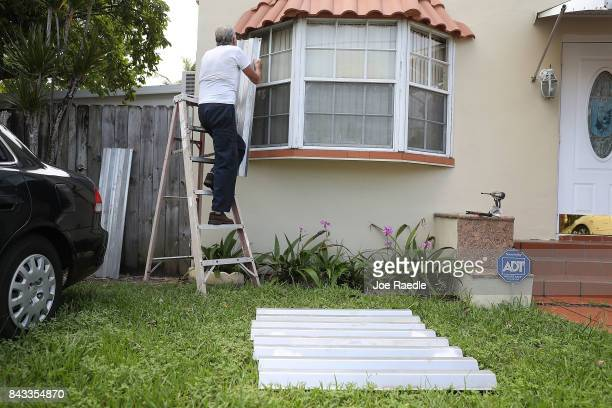 Gilberto Mojena puts up shutters as he prepares his house for Hurricane Irma on September 6 2017 in Miami Florida It's still too early to know where...