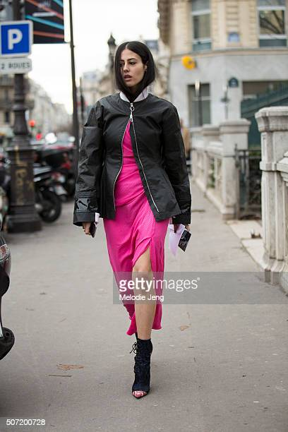Gilda Ambrosio of Grazia Italy wears a a black Dior bomber jacket zipped at the neck and a Alessandra Rich slit pink dress at the Jean Paul Gaultier...