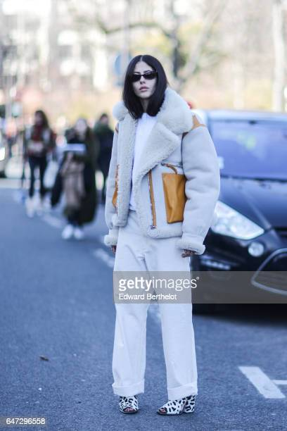 Gilda Ambrosio wears a coat with fur inner lining and white pants outside the Chloe show during Paris Fashion Week Womenswear Fall/Winter 2017/2018...