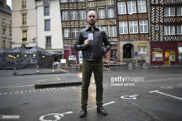 Gildas Lamette waiter in a café single with no children living in Rennes in northwest France poses with his voting card in Rennes on February 2 2017...