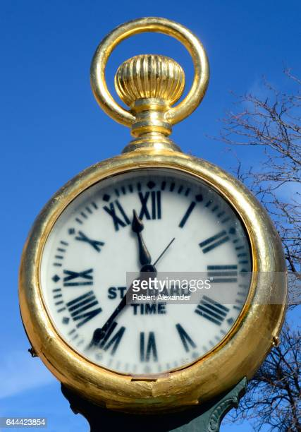 A gilded antique street clock showing 'standard time' stands at a corner in Santa Fe New Mexico Before it was relocated to the downtown street corner...