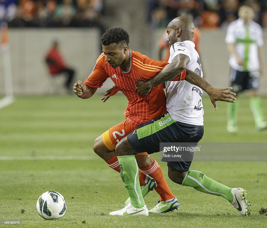 Giles Barnes #23 of Houston Dynamo fends off Felipe Baloy #23 of Santos Laguna as he brings the ball up the field during the second half at BBVA Compass Stadium on March 5, 2013 in Houston, Texas.