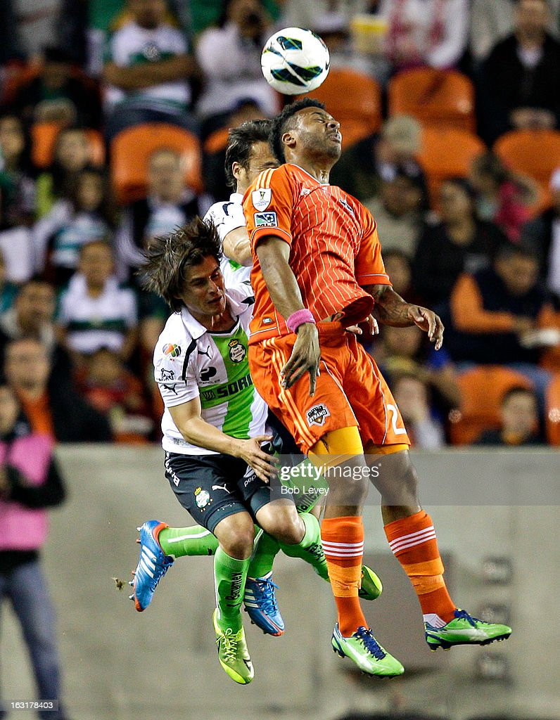 Giles Barnes #23 of Houston Dynamo goes up for a header with <a gi-track='captionPersonalityLinkClicked' href=/galleries/search?phrase=Nestor+Calderon&family=editorial&specificpeople=5639934 ng-click='$event.stopPropagation()'>Nestor Calderon</a> #11 during the first half at BBVA Compass Stadium on March 5, 2013 in Houston, Texas.