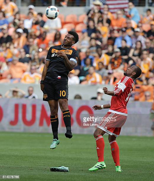 Giles Barnes of Houston Dynamo heads the ball away from Teal Bunbury of New England Revolution at BBVA Compass Stadium on March 6 2016 in Houston...