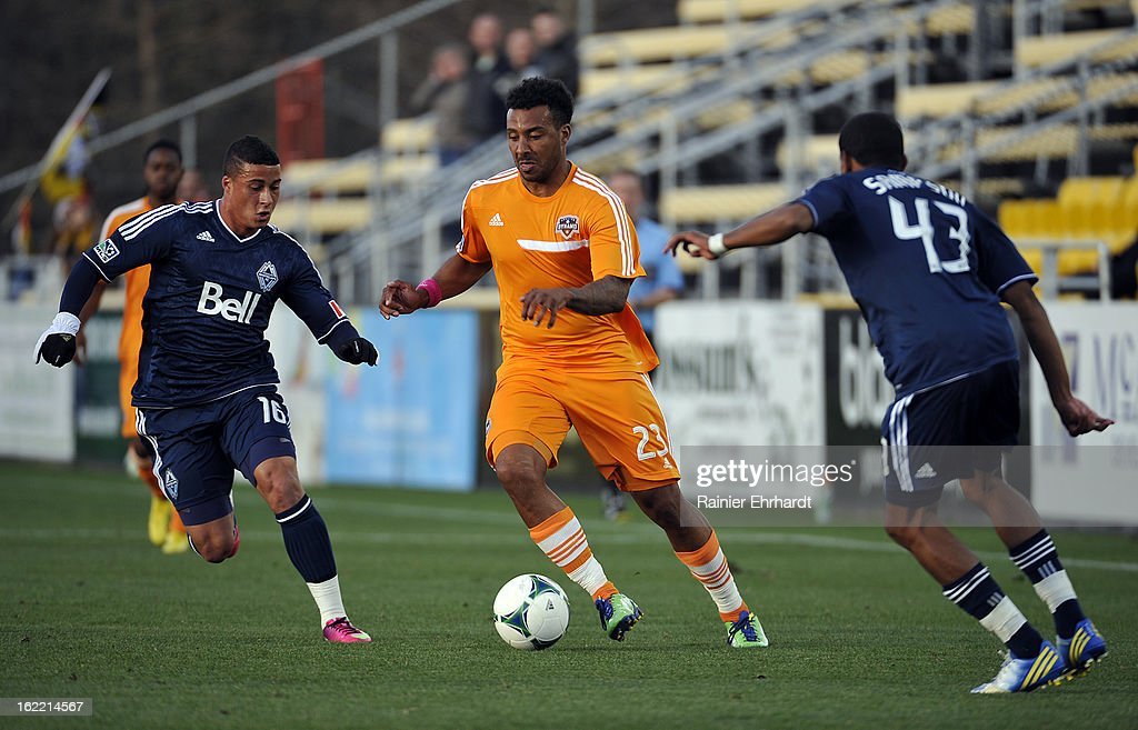 Giles Barnes #23 of the Houston Dynamo controls the ball as Erik Hurtado #16 of the Vancouver Whitecaps FC and teammate Ethen Sampson #43 defend during the first half of a game on February 20, 2013 in Charleston, North Carolina.