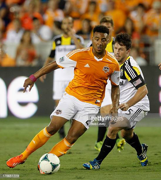 Giles Barnes of the Houston Dynamo dribbles the ball past Danny O'Rourke of the Columbus Crew at BBVA Compass Stadium on August 3 2013 in Houston...