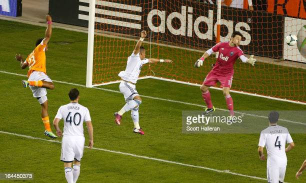 Giles Barnes of the Houston Dynamo scores a goal past Joe Cannon of the Vancouver Whitecaps during an MLS match at BBVA Compass Stadium on March 23...