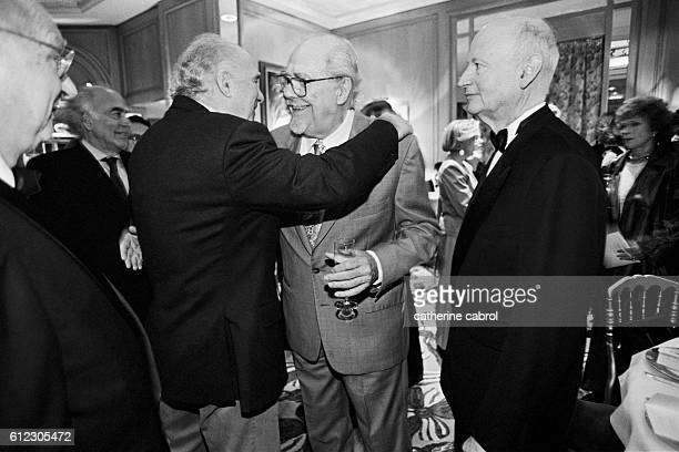 Gilles Jacob watches as Michel Piccoli hugs Robert Altman in greeting