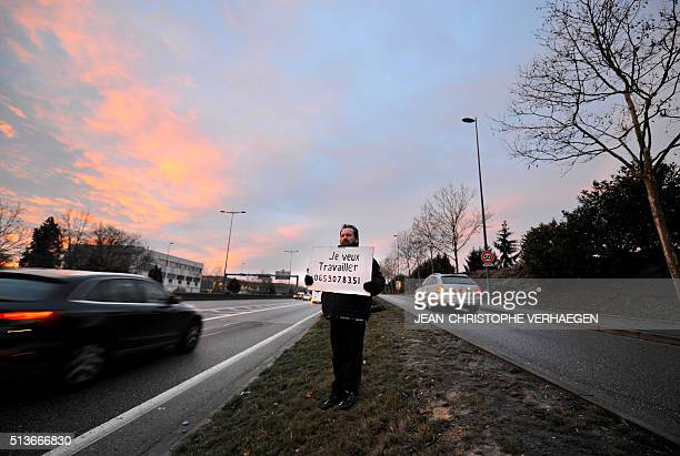 Gilles Latraye a 57 yearold jobseeker stands on February 29 along the highway in Nancy eastern France holding a placard which reads 'I want to work'...