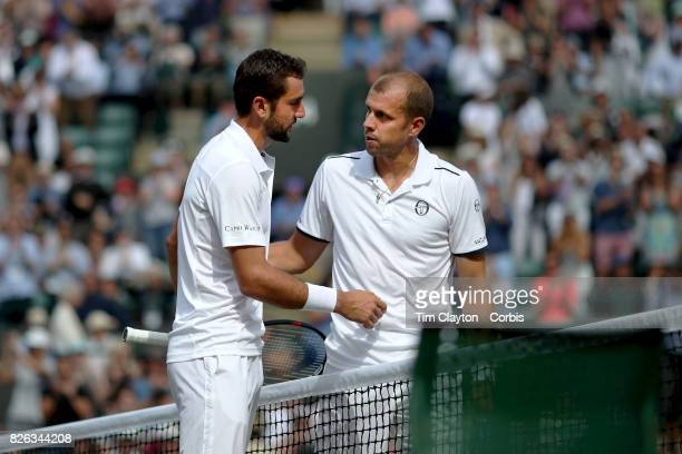Gilles Muller of Luxembourg congratulates Marin Cilic of Croatia on his win in the Mens' Singles Quarter Final match on Court One during the...