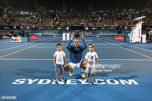 Gilles Muller of Luxembourg holds aloft the winners trophy with his sons Lenny and Nils after winning the men's final match against Daniel Evans of...