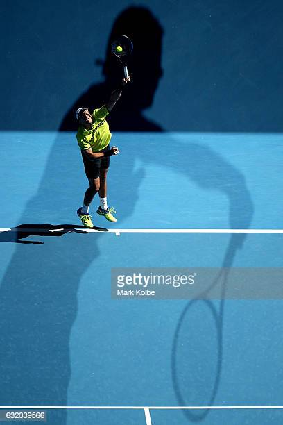 Gilles Muller of Luxembourg serves in the shadow of Milos Raonic of Canada in their second round match on day four of the 2017 Australian Open at...