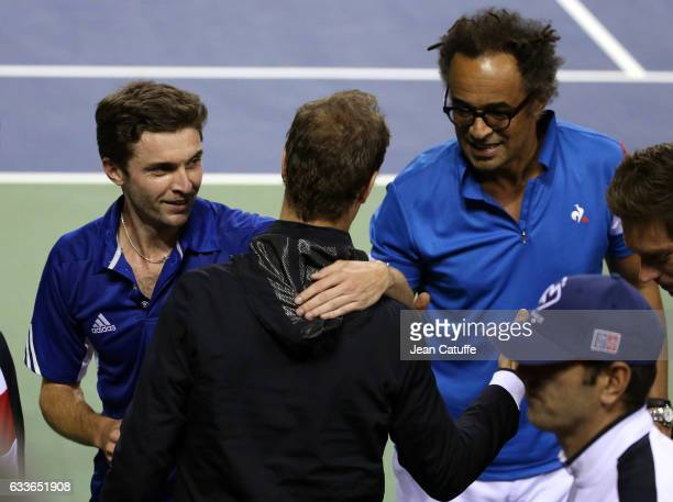 Gilles Simon and captain of Team France Yannick Noah greet teammates following Gilles' victory against Yoshihito Nishioka of Japan on day 1 of the...