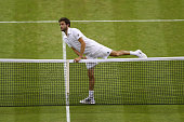 Gilles Simon of France crosses the net after victory in his Mens Singles Third Round match to console Gael Monfils of France during day six of the...