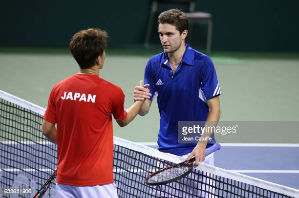 Gilles Simon of France greets Yoshihito Nishioka of Japan at the net following his victory on day 1 of the Davis Cup World Group first round tie...