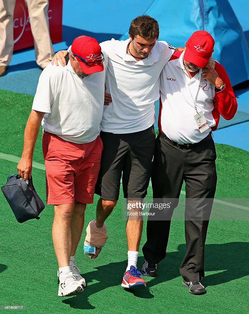 <a gi-track='captionPersonalityLinkClicked' href=/galleries/search?phrase=Gilles+Simon&family=editorial&specificpeople=548968 ng-click='$event.stopPropagation()'>Gilles Simon</a> of France leaves the court injured after his match against Richard Gasquet of France during day three of the AAMI Classic at Kooyong on January 10, 2014 in Melbourne, Australia.