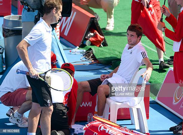 Gilles Simon of France reacts after injuring his ankle against compatriot Richard Gasquet and retires from their match at the invitational Kooyong...