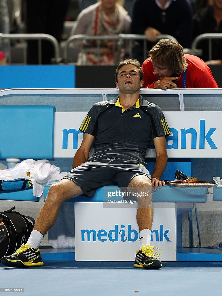 Gilles Simon (L) of France rests on his seat after winning his third round match against Gael Monfils of France in the 2013 Australian Open at Melbourne Park on January 19, 2013 in Melbourne, Australia.