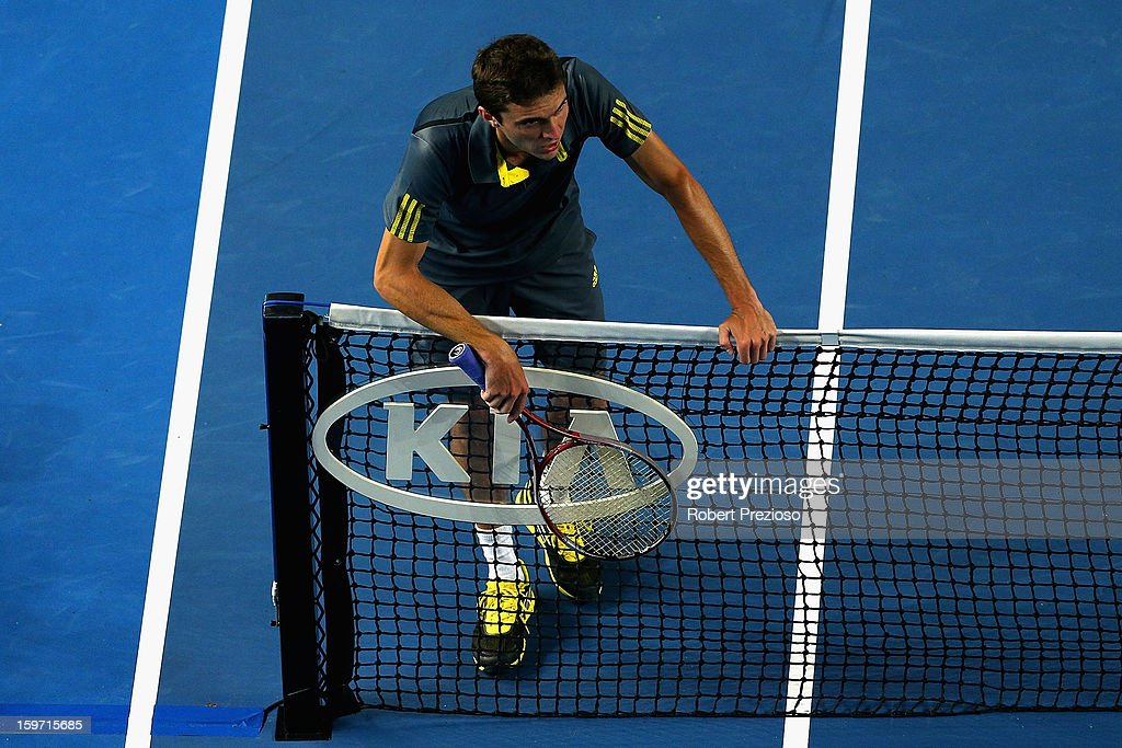 Gilles Simon of France rests on the net in his third round match against Gael Monfils of France during day six of the 2013 Australian Open at Melbourne Park on January 19, 2013 in Melbourne, Australia.