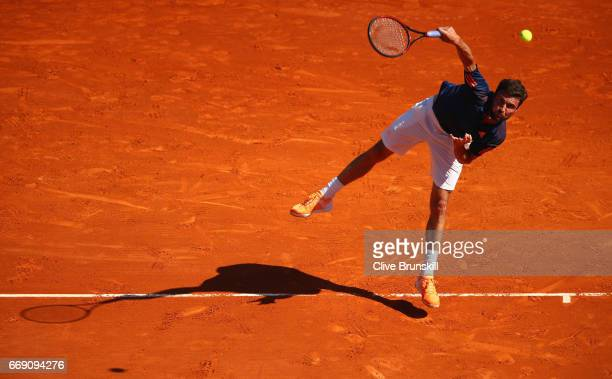 Gilles Simon of France serves against Malek Jaziri of Tunisia in their first round match on day one of the Monte Carlo Rolex Masters at MonteCarlo...