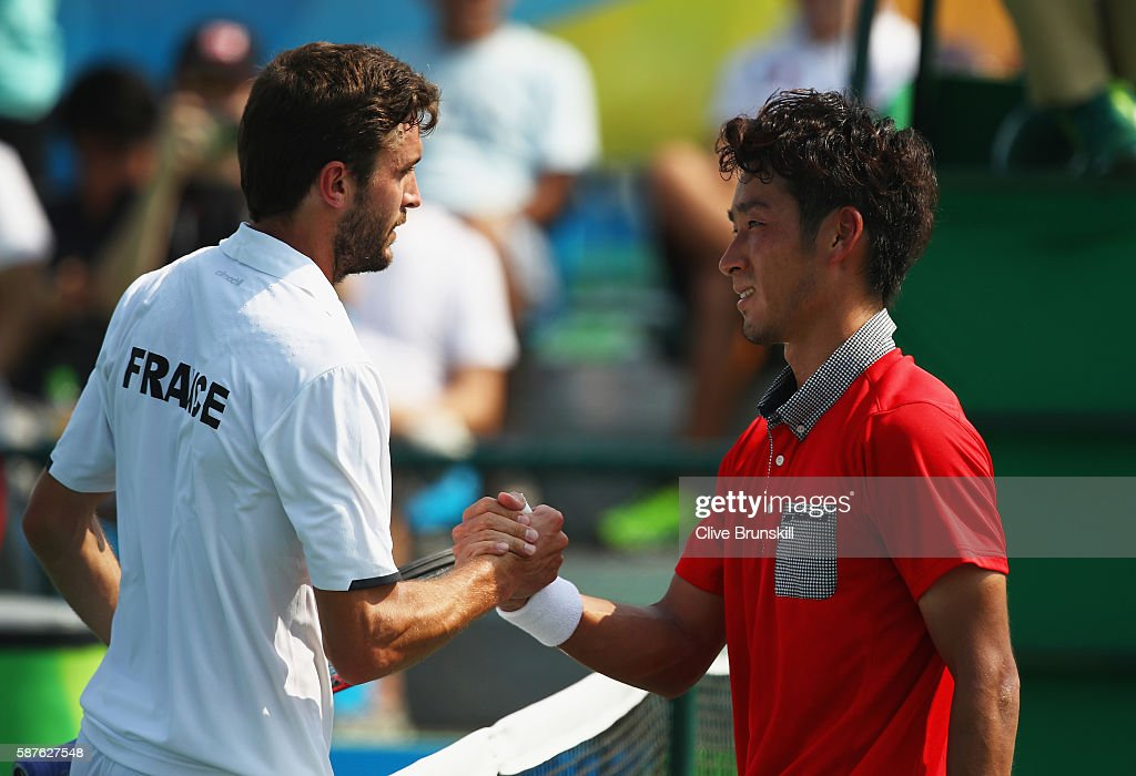 Gilles Simon of France shakes hands with Yuichi Sugita of Japan during the men's second round singles match on Day 4 of the Rio 2016 Olympic Games at...