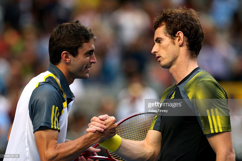 Gilles Simon of France (L) speaks to Andy Murray of Great Britain after Murray won their fourth round match during day eight of the 2013 Australian Open at Melbourne Park on January 21, 2013 in Melbourne, Australia.
