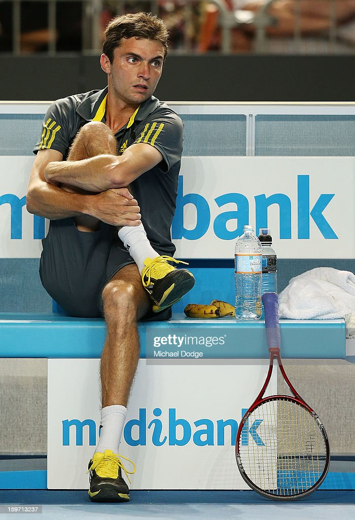 Gilles Simon of France stretches his leg in his third round match against Gael Monfils of France in the 2013 Australian Open at Melbourne Park on January 19, 2013 in Melbourne, Australia.