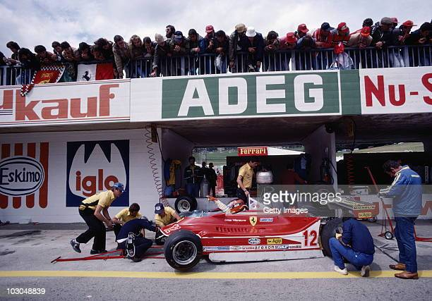 Gilles Villeneuve gestures for adjustments to be made on the Scuderia Ferrari SpA SEFAC Ferrari 312T4 as spectators look on during practice for the...