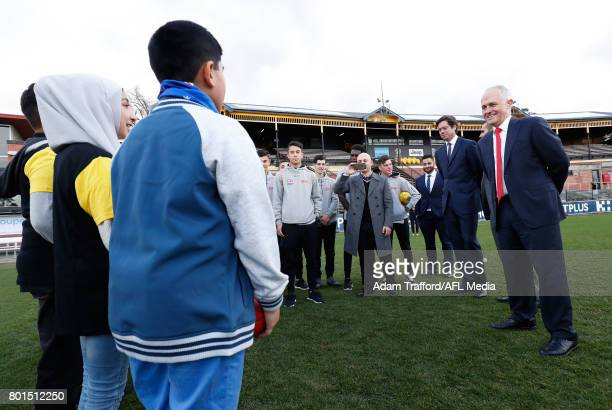 Gillon McLachlan Chief Executive Officer of the AFL Bachar Houli of the Tigers and Malcolm Turnbull Prime Minister of Australia listen to a song from...