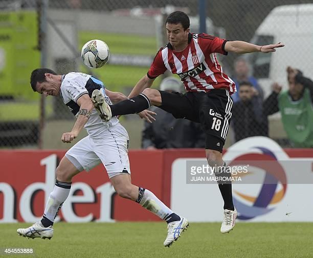Gimansia's defender Osvaldo Barsottini vies for the ball with Estudiantes' midfielder Leonardo Jara during the Copa Sudamericana 2014 second stage...