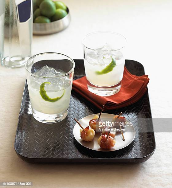 Gimlet cocktails and appetizers on tray