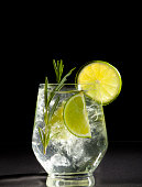 Glass with alcoholic drink with lime and ice on a black background.