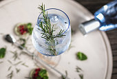 Decorated Gin Soda with a Rosemary Leaf on a wooden desk