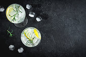 Alcohol drink (gin tonic cocktail) with lemon, rosemary and ice on rustic black stone table, copy space, top view. Iced drink with lemon and herbs.