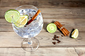 Gin tonic with lime slice, cinnamon sticks and peppercorns on wood background
