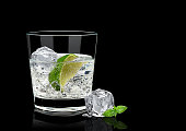 Gin tonic, lime and basil isolated on black background