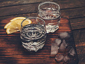 Gin tonic, vodka or rum with ice and lemon on wooden table. Retro styled background.