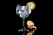 Gin tonic with lemmon and cinnamon on black background