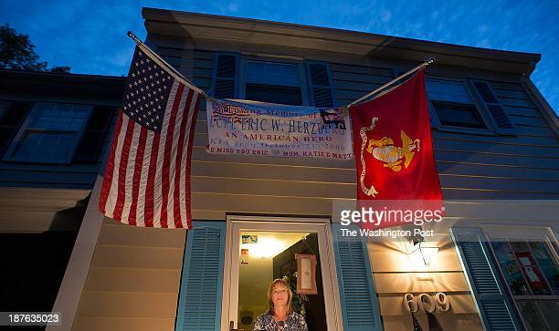 Gina Barnhurst mother of US Marine Lance Cpl Eric W Herzberg pose for a photo at her front door where a banner and flags memorialize her son on...