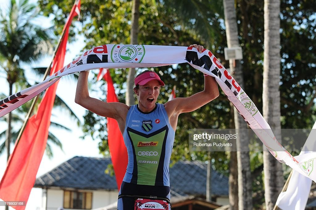 Gina Crawford of New Zealand raises the finish tape as she took runner-up position in the Meta Man Iron Distance Triathlon on August 31, 2013 in Bintan Island, Indonesia.