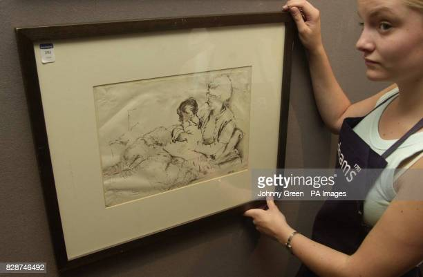 Gina Holme who is on work experience at Bonhams auction house central London straightens 'fifth Beatle' Stuart Sutcliffe's ink drawing of his mother...