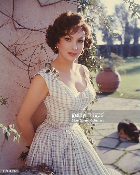 Gina Lollobrigida Italian actress wearing a lowcut sleeveless printed summer dress as she poses against a garden wall circa 1955